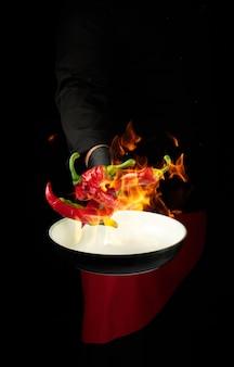 Un chef en uniforme noir tient une poêle ronde et jette des piments rouges et verts entiers dans un feu brûlant