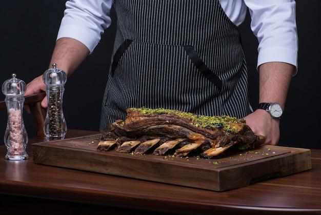 Un chef en uniforme sert un plat de viande sur un plateau en bois