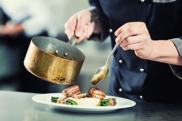 Chef versant la sauce sur plat dans la cuisine du restaurant