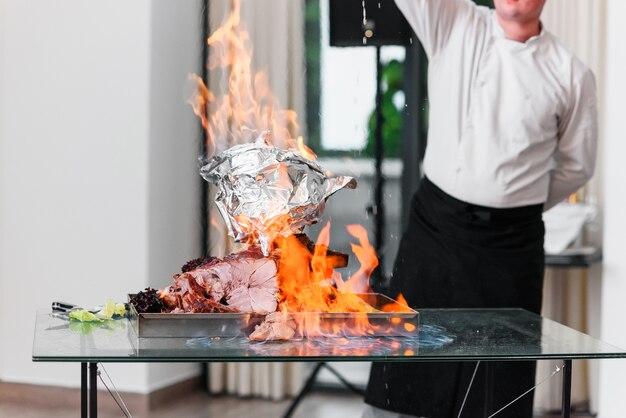 Le chef verse de l'alcool à la dinde au four sur une assiette au feu. dinde rôtie.