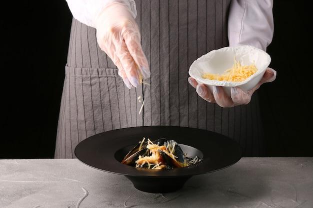 Le chef verse du fromage sur les pâtes. chef de femme.