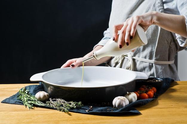 Le chef verse de l'huile d'olive dans un plat allant au four.