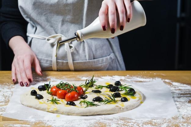 Le chef verse de l'huile d'olive sur la focaccia crue.