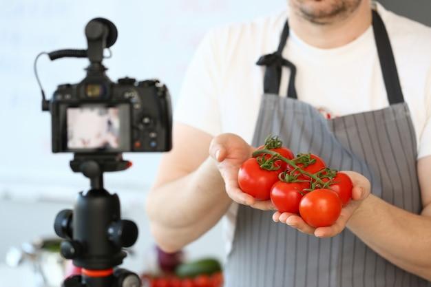 Chef vlogger montrant l'ingrédient de tomates mûres. homme en tablier enregistrant un gros légume rouge sur un caméscope pour un vlog culinaire.