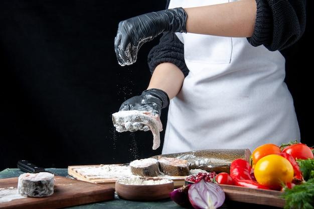 Chef de vue de face couvrant des tranches de poisson avec de la farine de légumes frais sur un bol de farine de planche de bois sur une table de cuisine