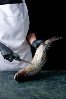 Chef vue de face en tablier blanc tenant du poisson frais et un couteau sur la table