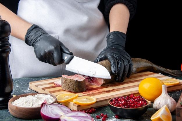 Chef vue de face en tablier coupant du poisson cru sur un bol de farine de planche à découper sur une table de cuisine