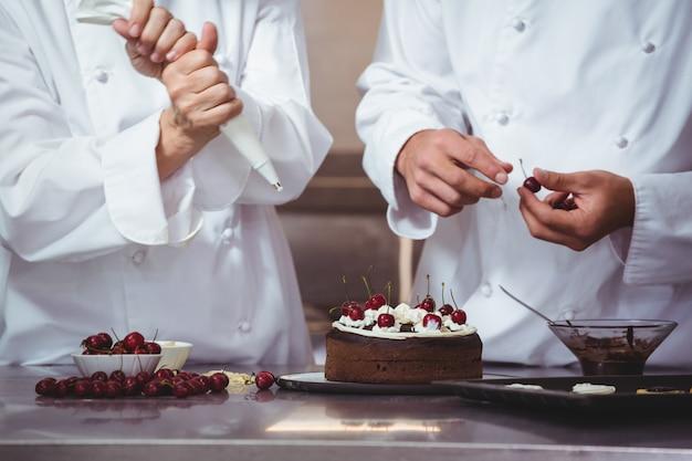 Chefs décorer un gâteau qu'ils viennent de faire