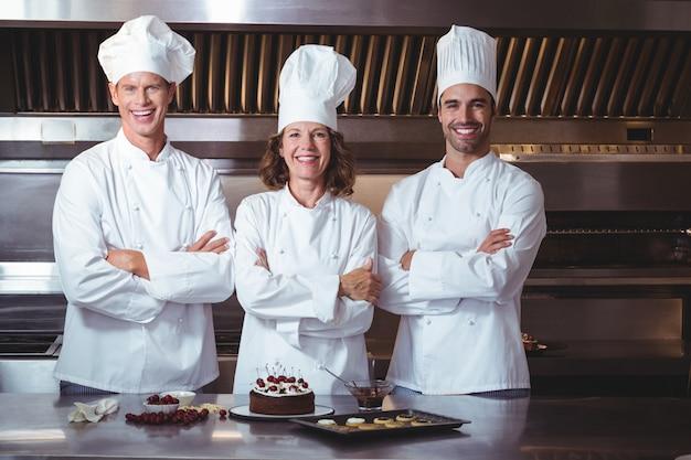 Chefs heureux et fiers de présenter le gâteau qu'ils viennent de faire