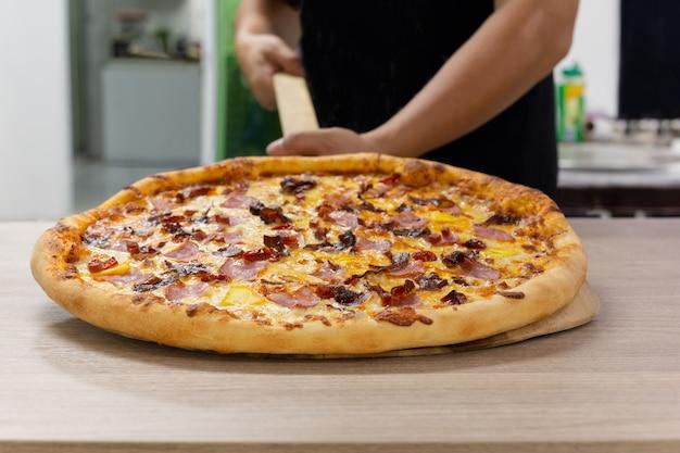 Chefs main tenant une pizza hawaïenne sur une planche de bois.