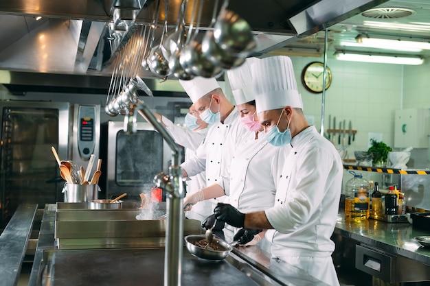 Les chefs portant des masques de protection et des gants préparent la nourriture dans la cuisine d'un restaurant ou d'un hôtel.
