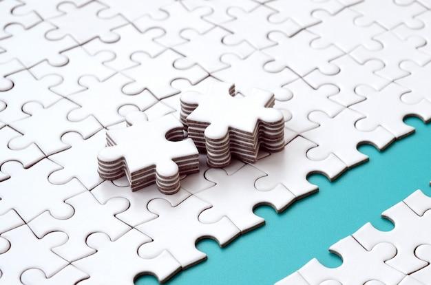 Le chemin bleu est posé sur la plateforme d'un puzzle plié en blanc.