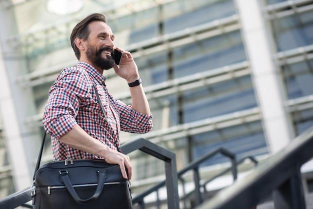 Chemin du bureau. agréable homme souriant, parler au téléphone tout en allant travailler