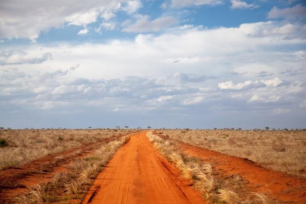 Chemin du sol rouge, ciel bleu avec des nuages, paysage du kenya