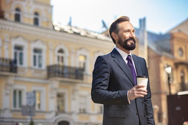 Chemin du succès. taille d'un homme d'affaires positif, boire du café tout en allant travailler