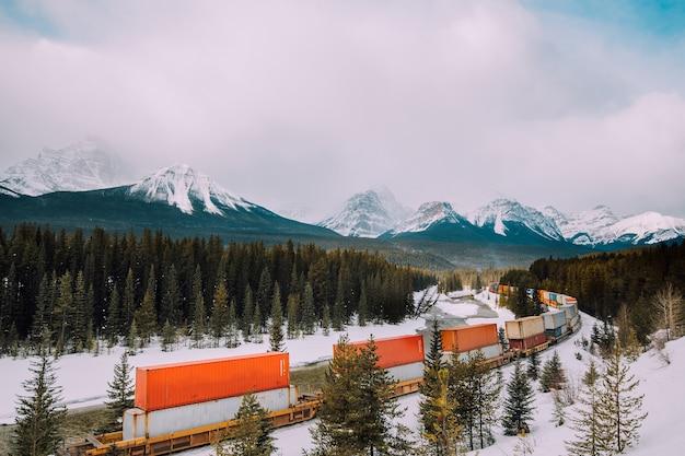 Chemin de fer courbe de morant et train avec fond de montagnes roakie canadiennes