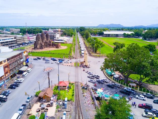Chemin de fer près des sites historiques avec une voiture en stationnement en attente du passage du train