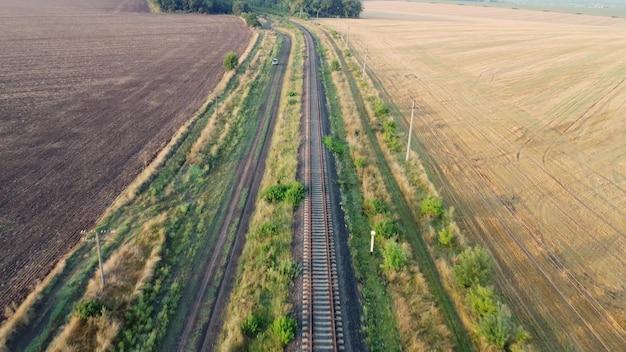 Chemin de fer à travers champs et forêts. une petite voiture sur un chemin de terre.