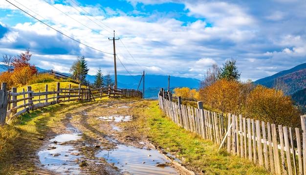 Un chemin le long de la crête d'une colline avec une grande flaque d'eau et une vieille clôture contre une forêt et un ciel