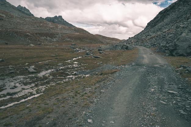 Chemin de montagne avec ciel orageux et vue panoramique.