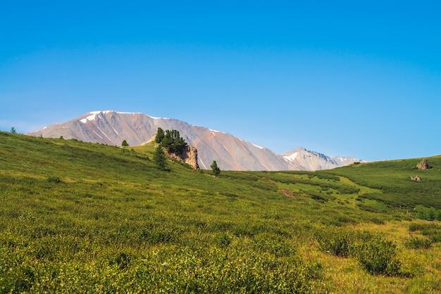 Chemin des montagnes géantes avec de la neige à travers la vallée verte sous un ciel bleu clair