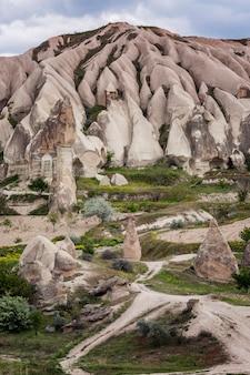Un chemin parmi les falaises roses de la cappadoce. tourisme et voyages. beau paysage. verticale.
