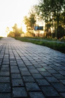 Le chemin de pavé gris s'éloigne de la perspective au coucher du soleil