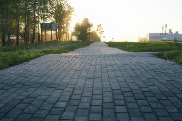 Le chemin de pavé s'éloigne de la perspective au coucher du soleil