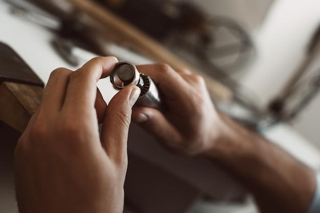 Sur le chemin de la perfection, les mains des joailliers masculins faisant une bague en argent sur son établi