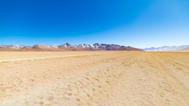 Chemin de terre à haute altitude avec désert sablonneux et chaîne de volcan stérile sur les hauts plateaux andins