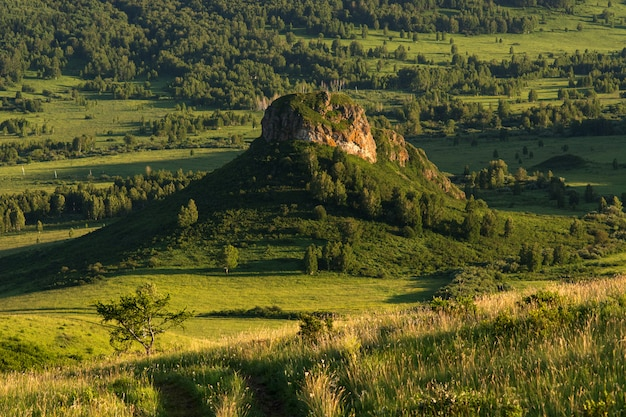 Le chemin de terre mène à la montagne. chapeau de montagne.