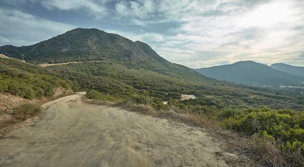 Chemin de terre de montagne étroit avec paysage derrière une riche végétation sous un ciel nuageux