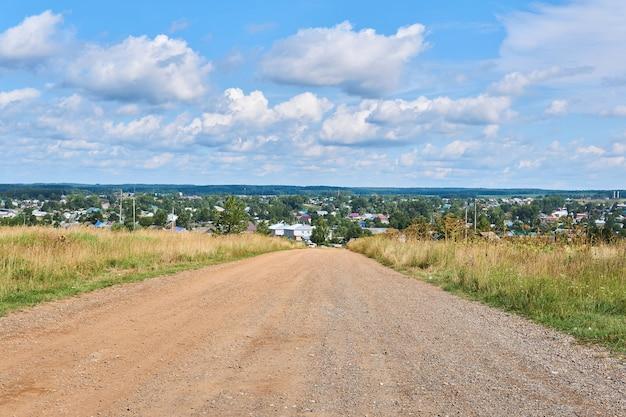Chemin de terre parmi les champs un jour d'été menant au village en arrière-plan