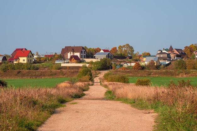 Un chemin de terre vide jusqu'à une colline avec des cottages. russie.