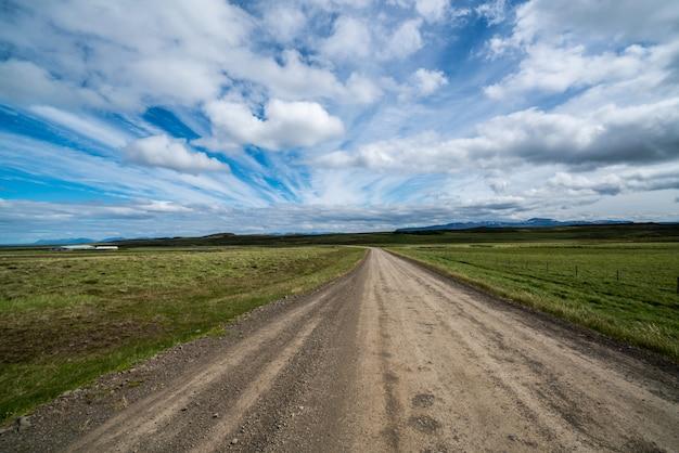 Chemin de terre vide à travers le paysage de campagne.
