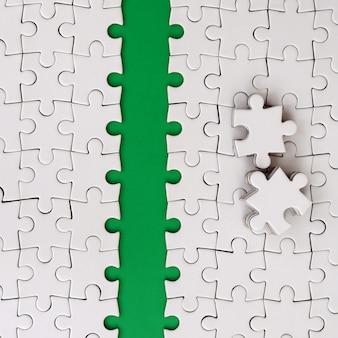 Le chemin vert est posé sur la plateforme d'un puzzle plié en blanc.