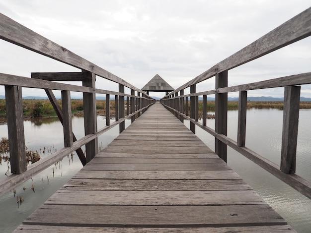 Chemin d'un vieux pont en bois avec pavillon entouré d'un bel étang et d'une montagne.