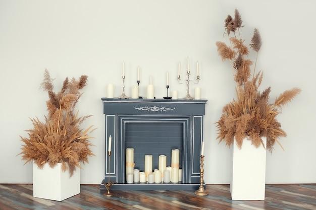 Cheminée artificielle décorée de diverses bougies décoratives et herbes décoratives sèches