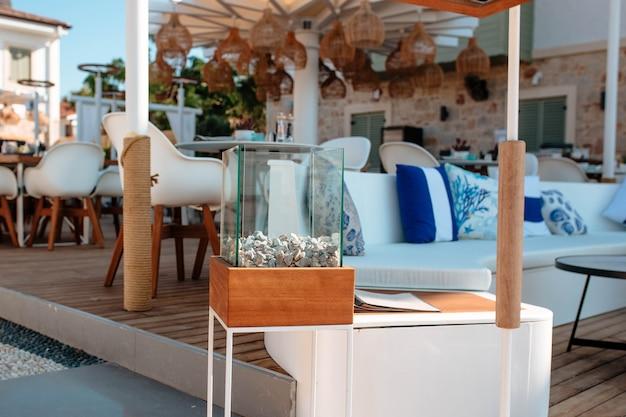 Une cheminée artificielle moderne en verre rempli de galets se dresse dans la rue à l'entrée du restaurant. le concept d'entreprise de restaurants d'hôtels.
