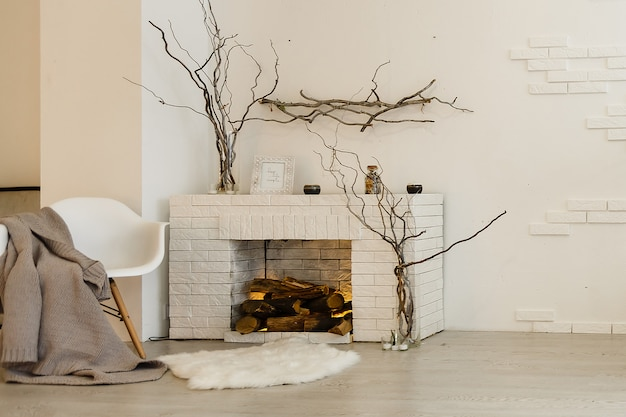 Cheminée blanche dans la salle lumineuse avec décoration de noël