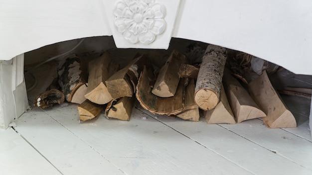 Cheminée blanche décorée avec du bois de chauffage