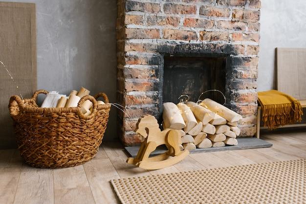 Cheminée en brique rouge avec du bois de chauffage et un panier de bois de chauffage à proximité, cheval jouet en bois pour enfants