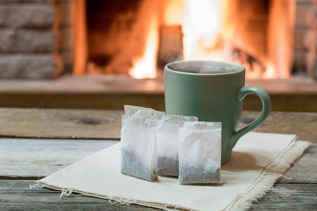 Cheminée confortable et une tasse de thé avec des sachets de thé