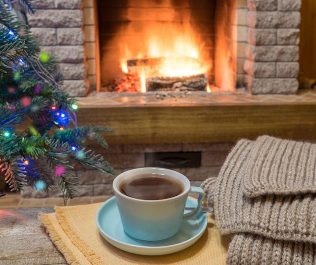 Cheminée confortable et une tasse de thé sur une table en bois, dans une maison de campagne, vacances d'hiver.