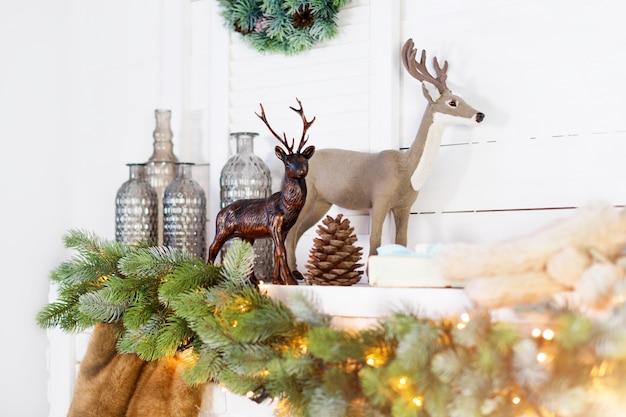 Cheminée avec décorations de noël. scène d'hiver confortable. détails intérieurs blancs avec lumières.