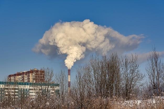 Une cheminée fumante à côté de bâtiments résidentiels contre un ciel bleu