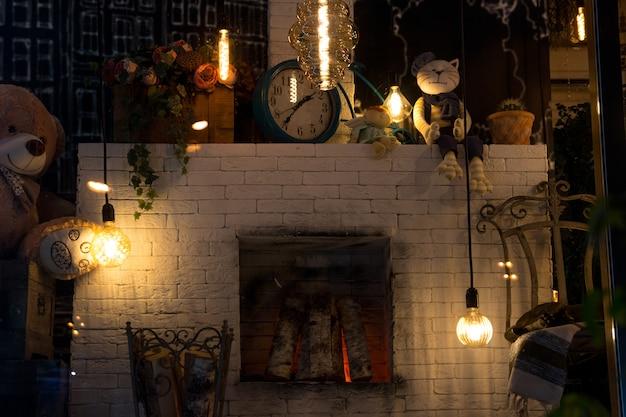 Une cheminée inondée dans la maison à l'extérieur de la fenêtre. une pièce intérieure chaleureuse avec des lampes suspendues