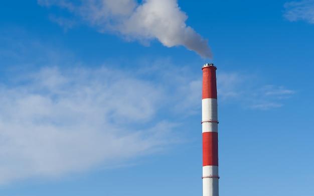 Cheminées fumantes rouges et blanches de l'usine sur ciel bleu.