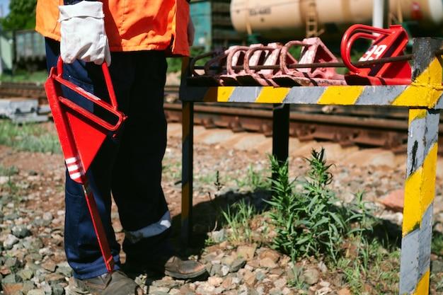 Un cheminot dans un gilet de signalisation orange et les bras tient dans sa main un sabot de frein rouge