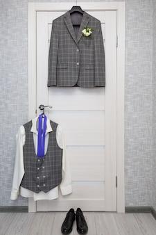 Une chemise blanche et une cravate violette, des chaussures noires sont suspendues à la porte